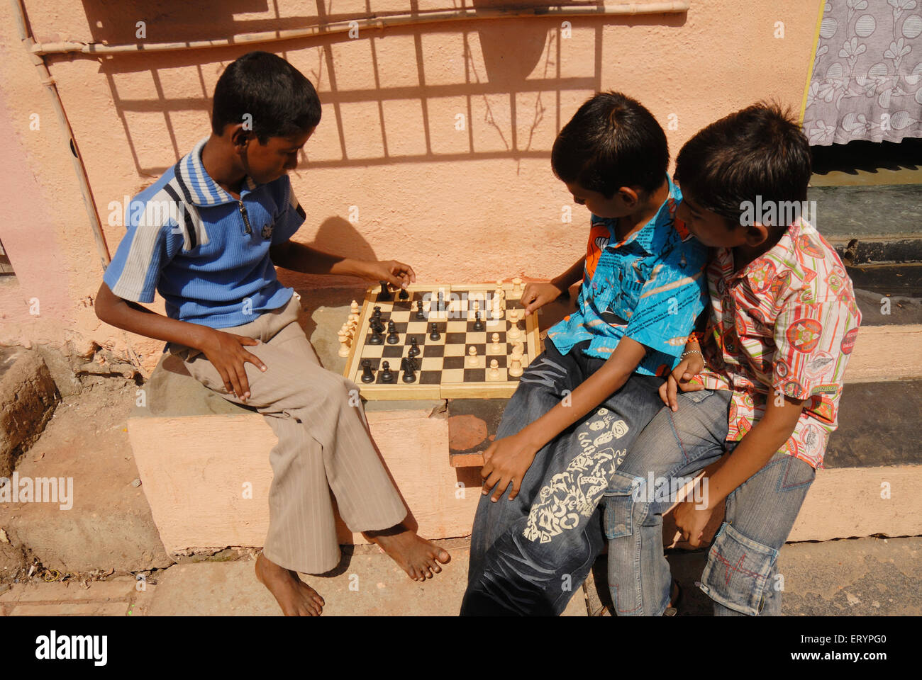 School children play game of chess during their vacations outside their homes in Bombay Mumbai ; Maharashtra ; India - Stock Image