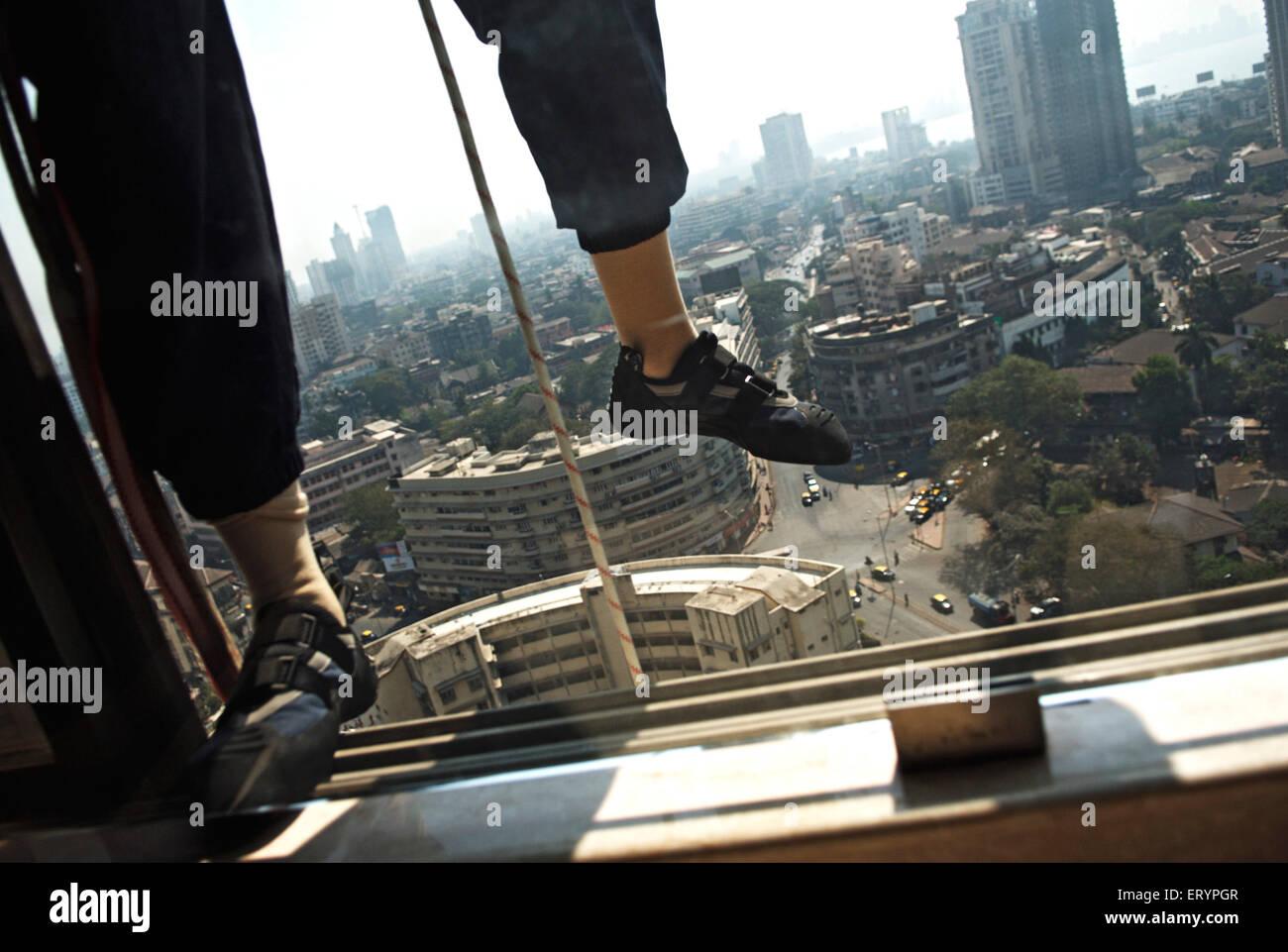 Worker tries to climb on building ; Bombay Mumbai  ; Maharashtra  ; India 25 Jan 2009 - Stock Image