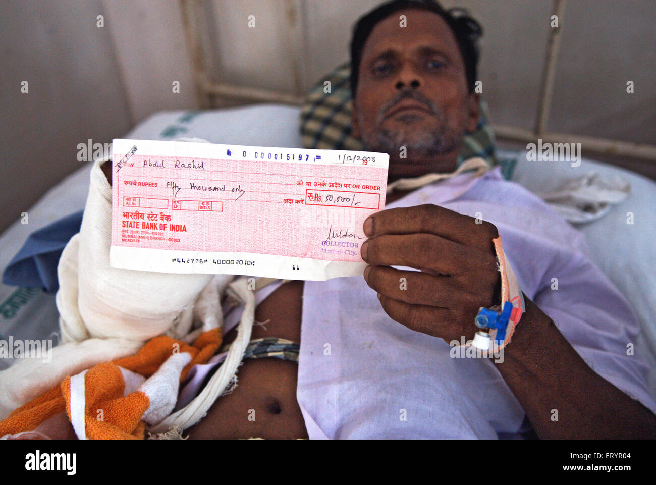 Abdul rashid showing compensation cheque victim of terrorist attack by deccan mujahedeen in Bombay Mumbai - Stock Image