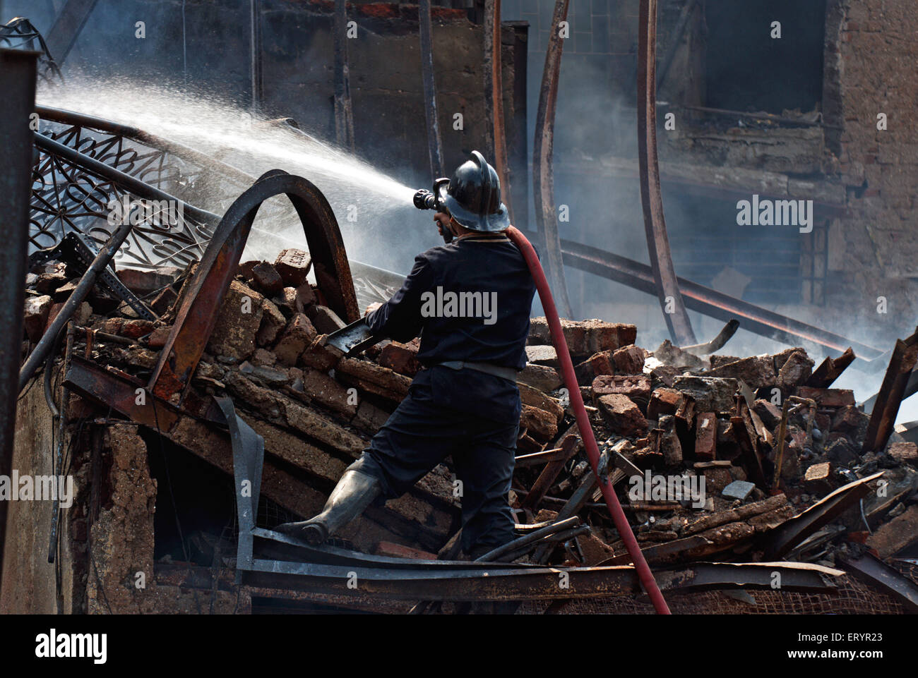 Firefighter dousing fire in Behrampada slums ; Bandra ; Bombay Mumbai ; Maharashtra ; India 18 June 2009 - Stock Image