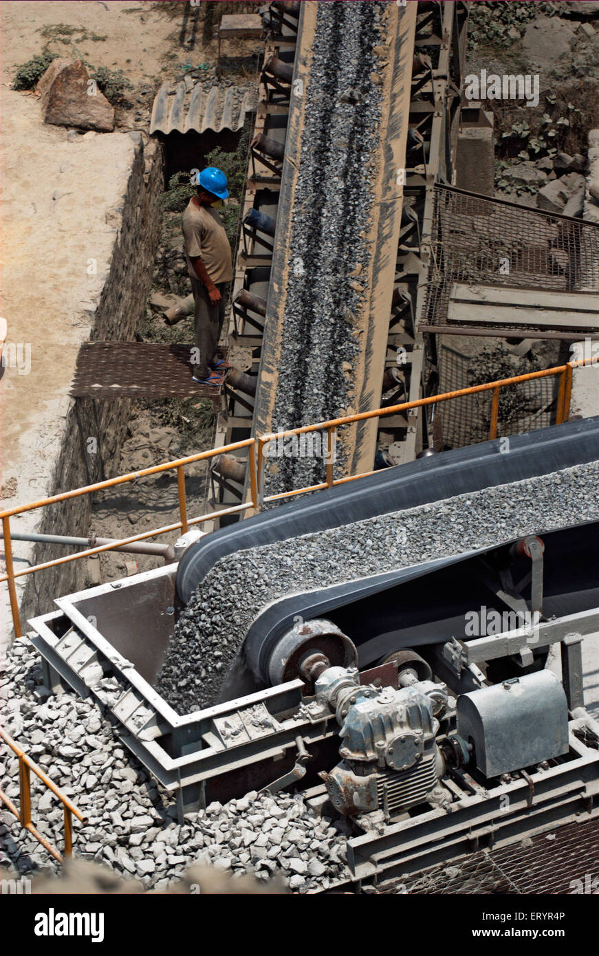 Worker inspecting crushed stones on conveyor belt on bypass site ; Madras Chennai ; Tamil Nadu ; India 17 July 2008 - Stock Image