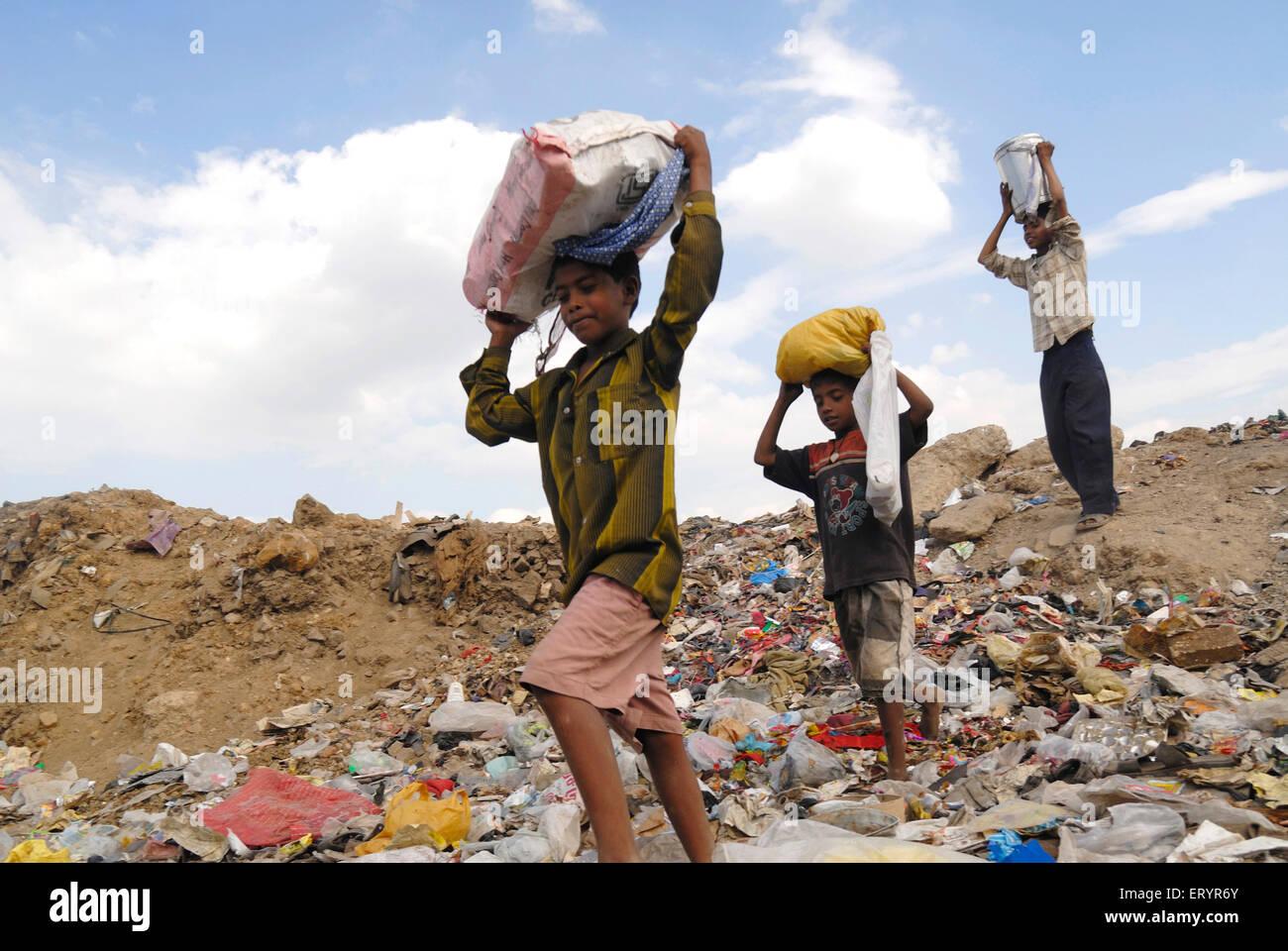 Rag pickers carrying load in dumping ground Deonar Bombay Mumbai Maharashtra India - Stock Image