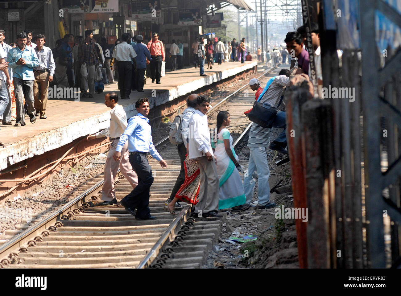 Commuter dangerously crossing railway tracks in Bombay Mumbai ; Maharashtra ; India - Stock Image
