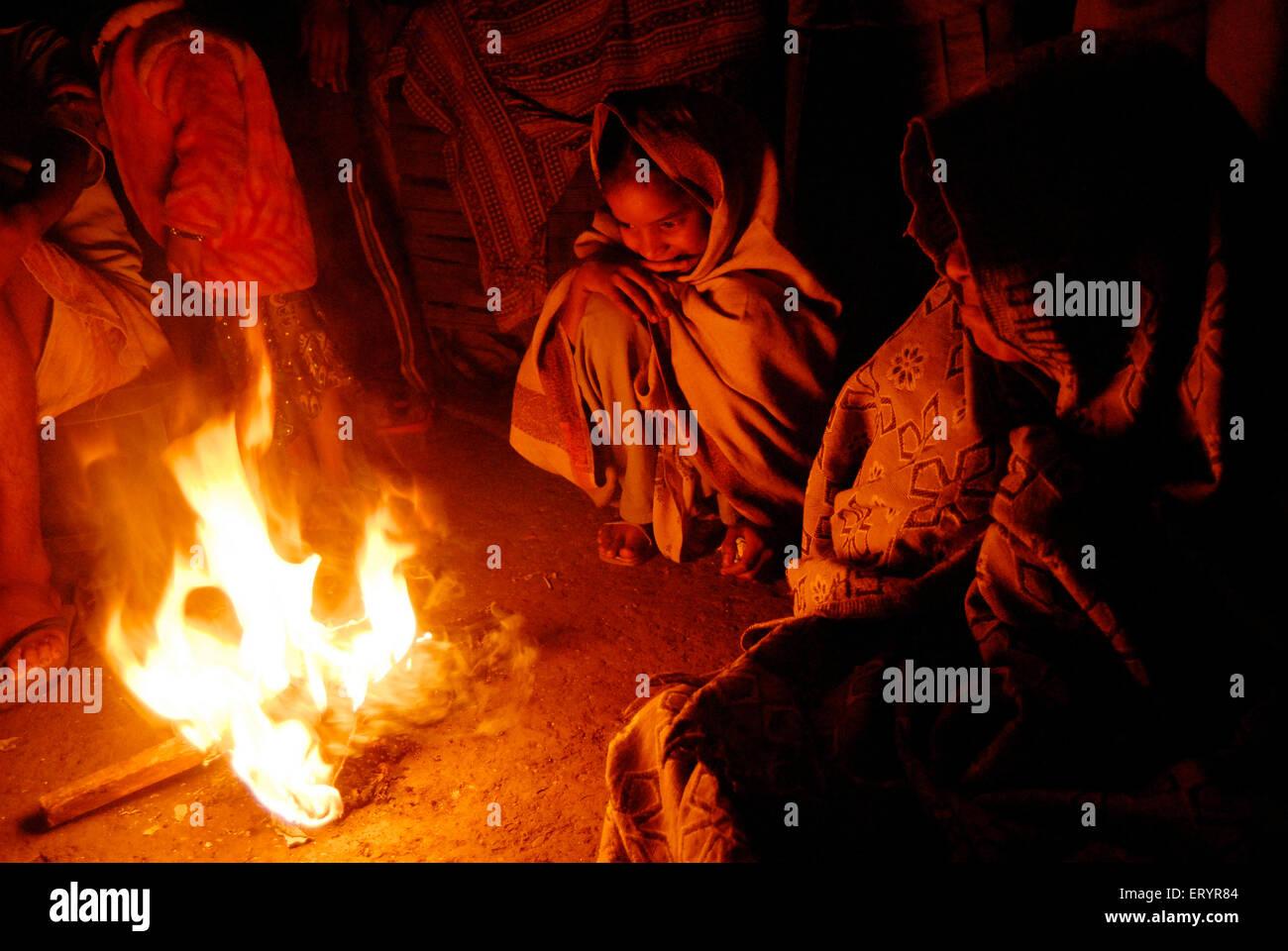 Hutment or slum dwellers sit around bonfire warming in winter season - Stock Image