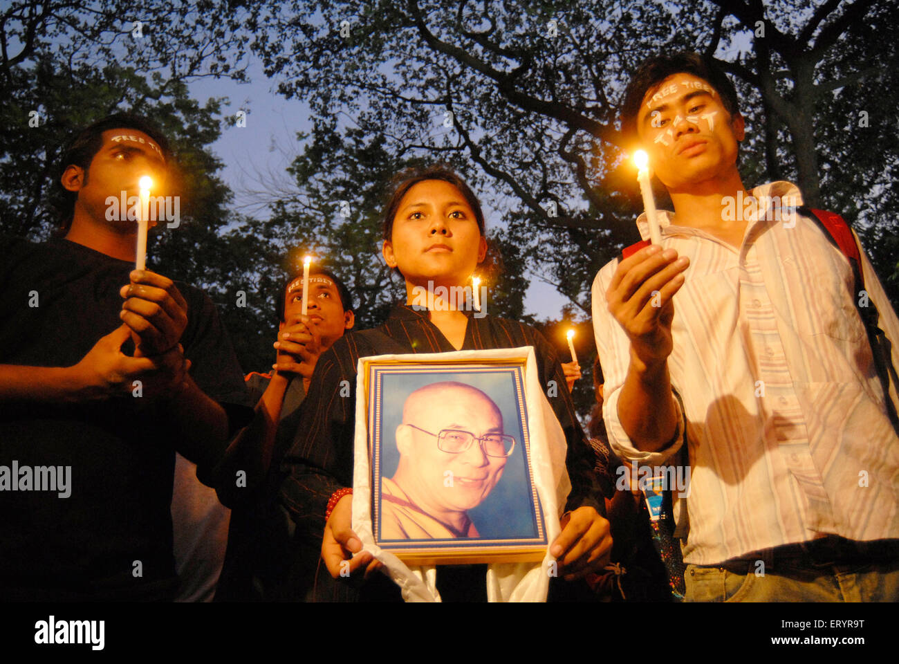 Tibetans holding photograph of Dalai Lama and candles protesting against Chinese crackdown in Tibet ; Bombay - Stock Image