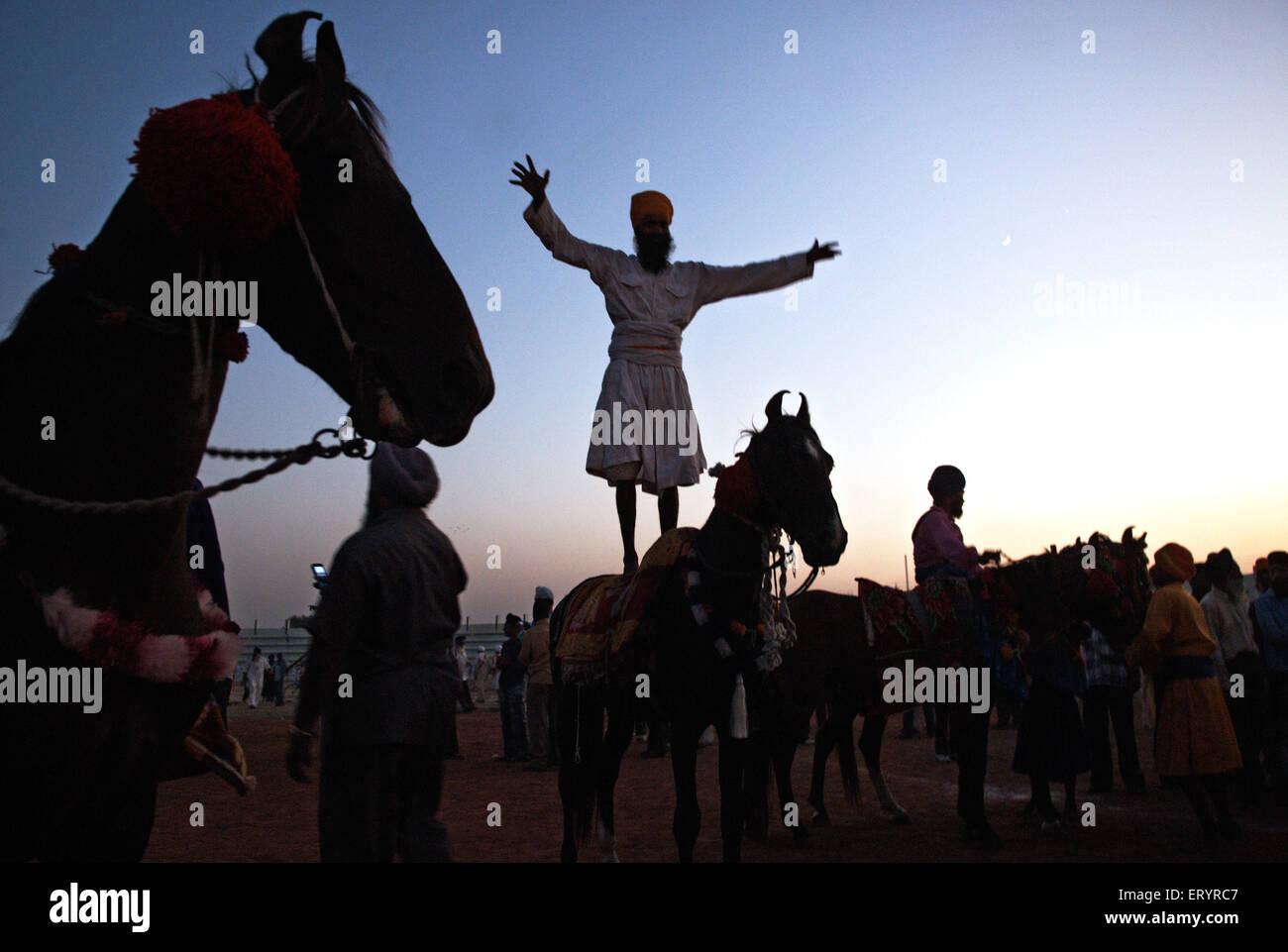Nihang sikh warrior performing stunts in celebrations of consecration of sikh guru granth sahib ; Nanded - Stock Image