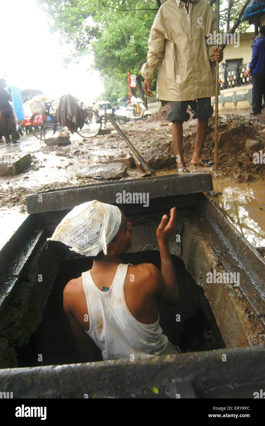 Worker cleans choked manhole during rainy season in Bombay Mumbai ; Maharashtra ; India - Stock Image
