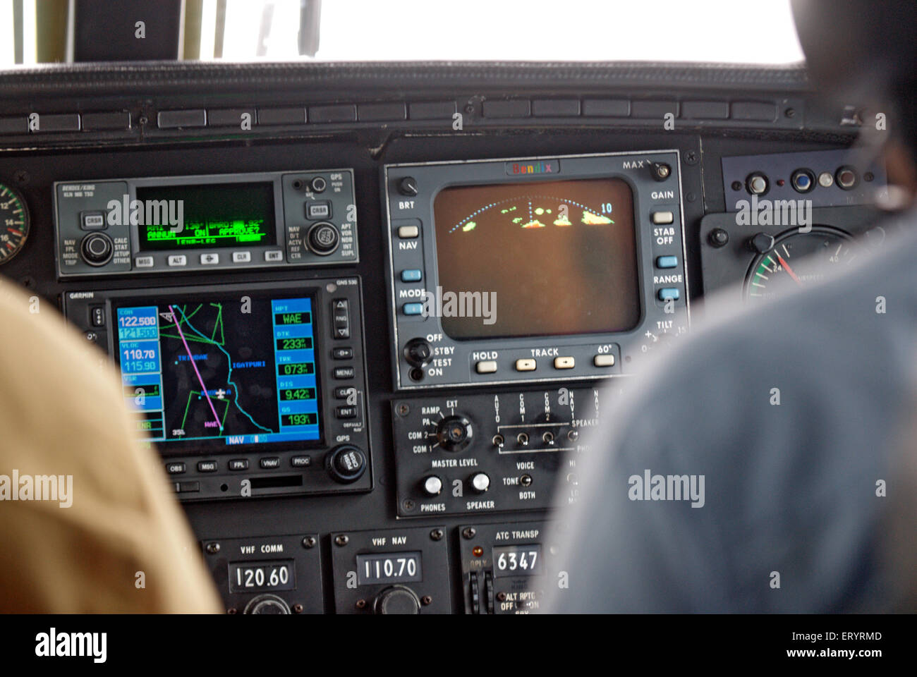 Pilots in cockpit of piper aircraft checking navigation ; India - Stock Image