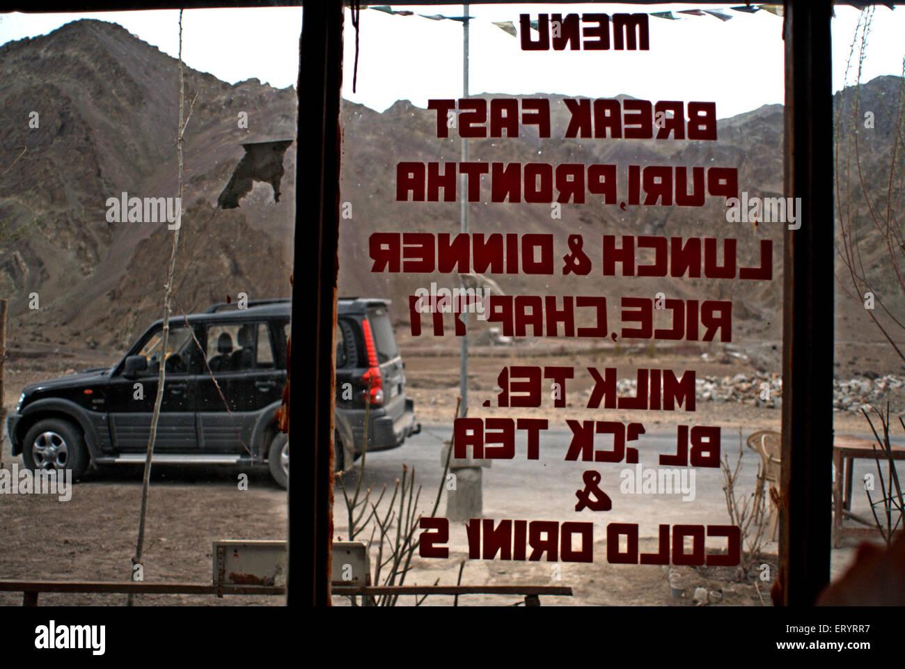 Menu written on glass door of hotel ; Ladakh ; Jammu and Kashmir ; India 9 April 2008 - Stock Image