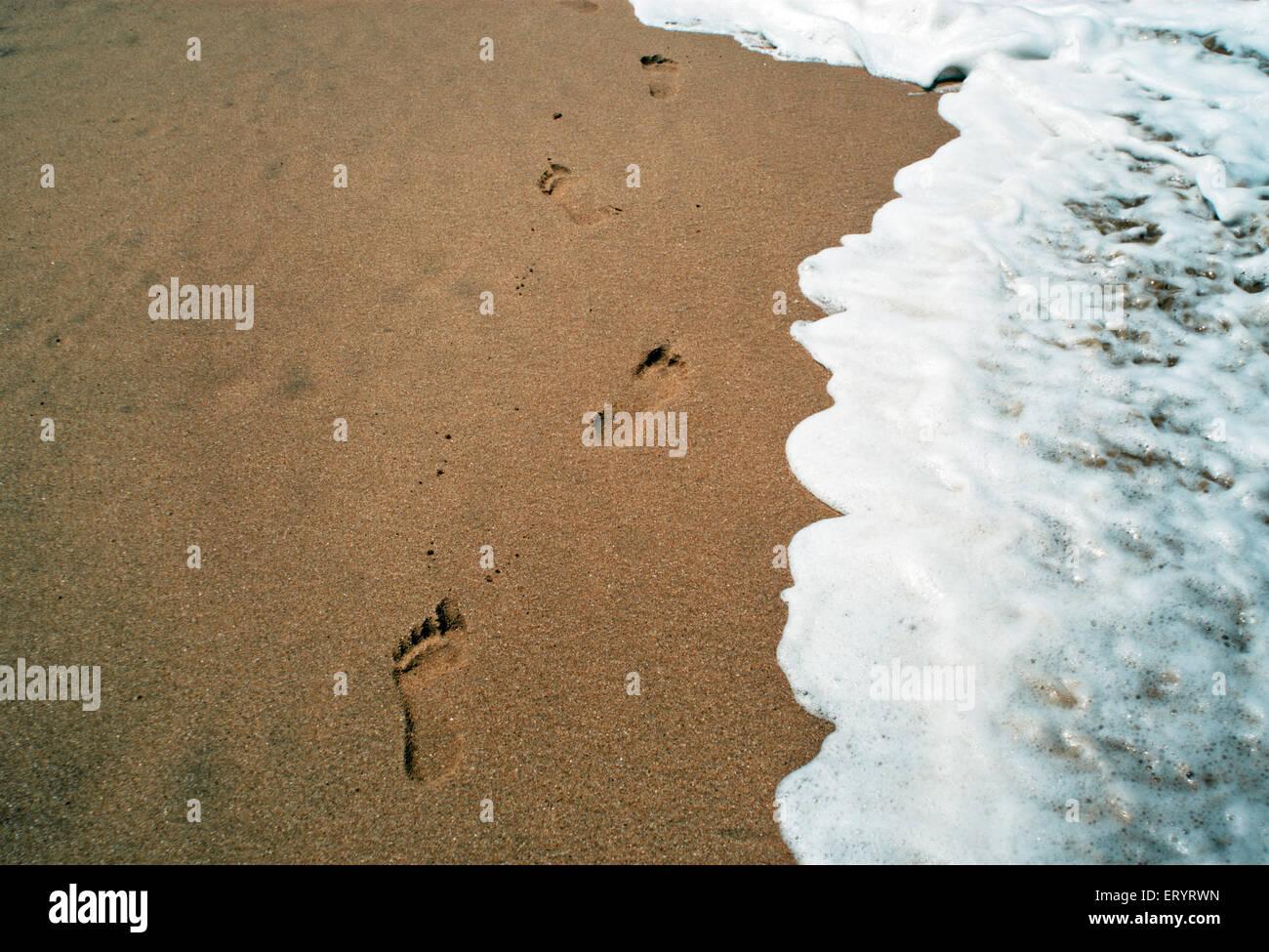 Surf near footprints at anjuna beach ; Goa ; India 8 May 2008 - Stock Image