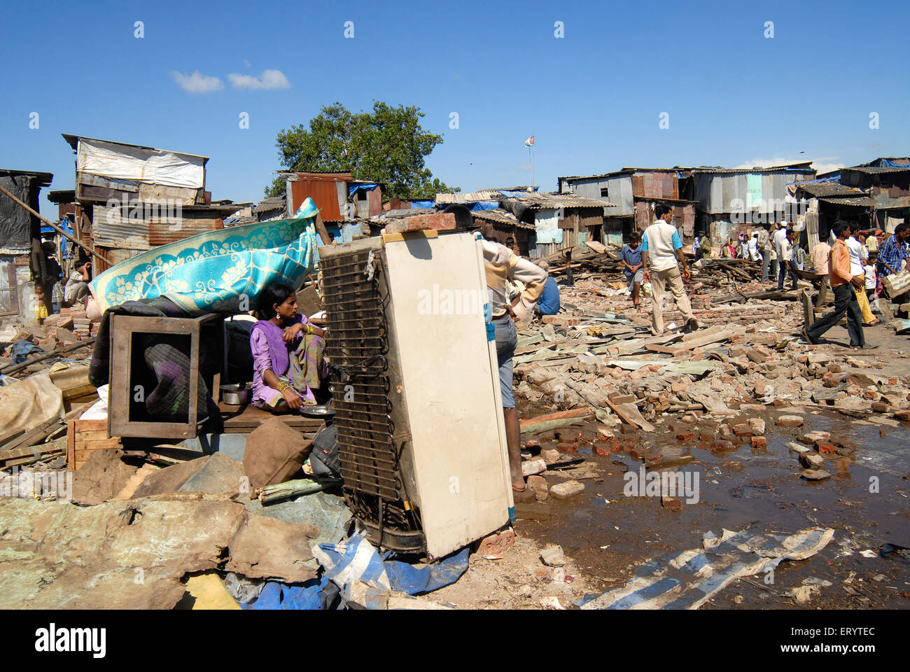 Slum dwellers sitting with their belongings after demolition of slums on Sahar airport Chatrapati Shivaji International - Stock Image