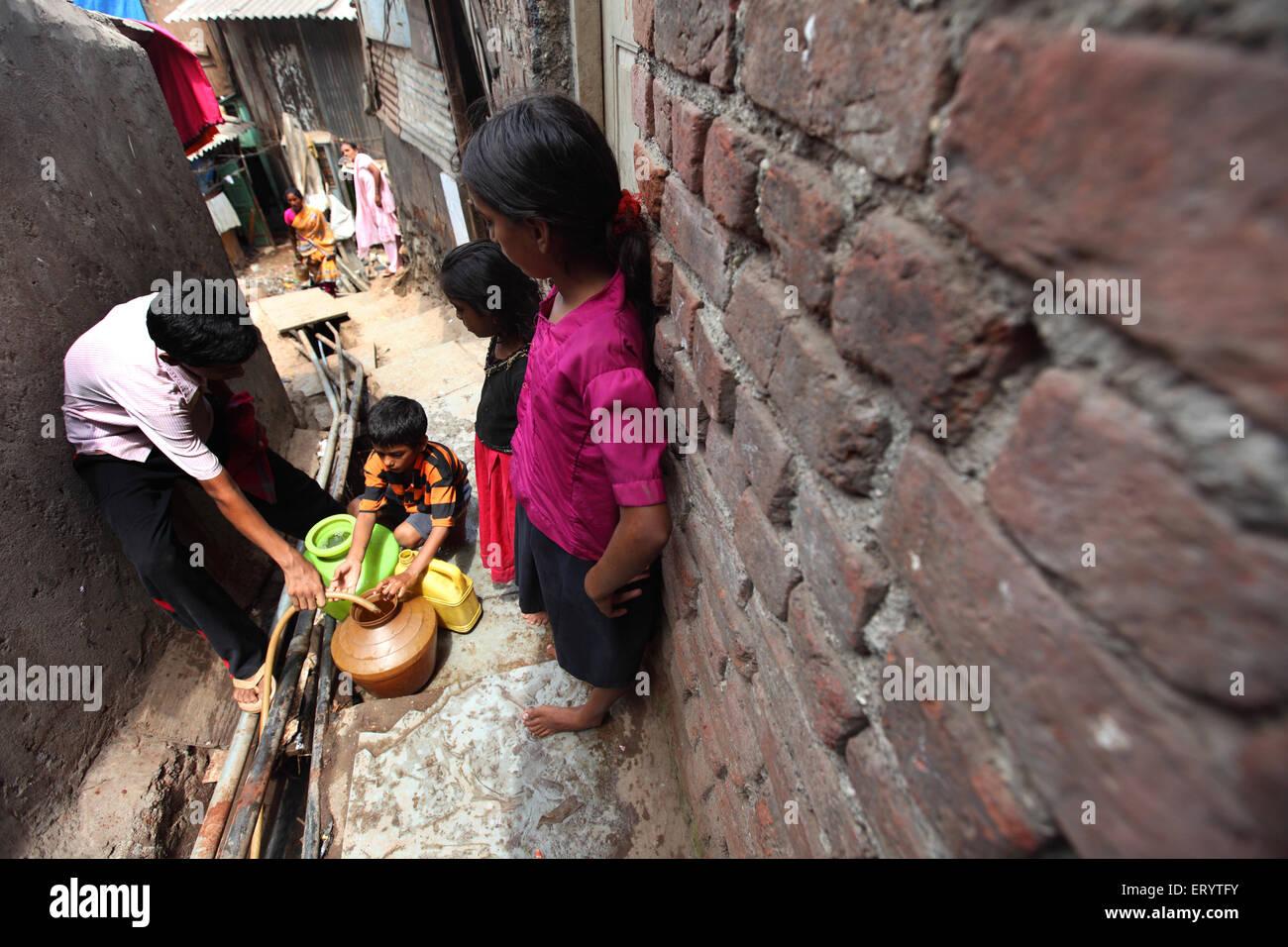 Slum dwellers filling water from pipe in Bombay Mumbai ; Maharashtra ; India - Stock Image