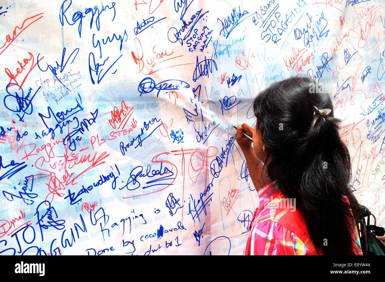 Student signing on anti ragging banner ; Bombay Mumbai ; Maharashtra ; India - Stock Image