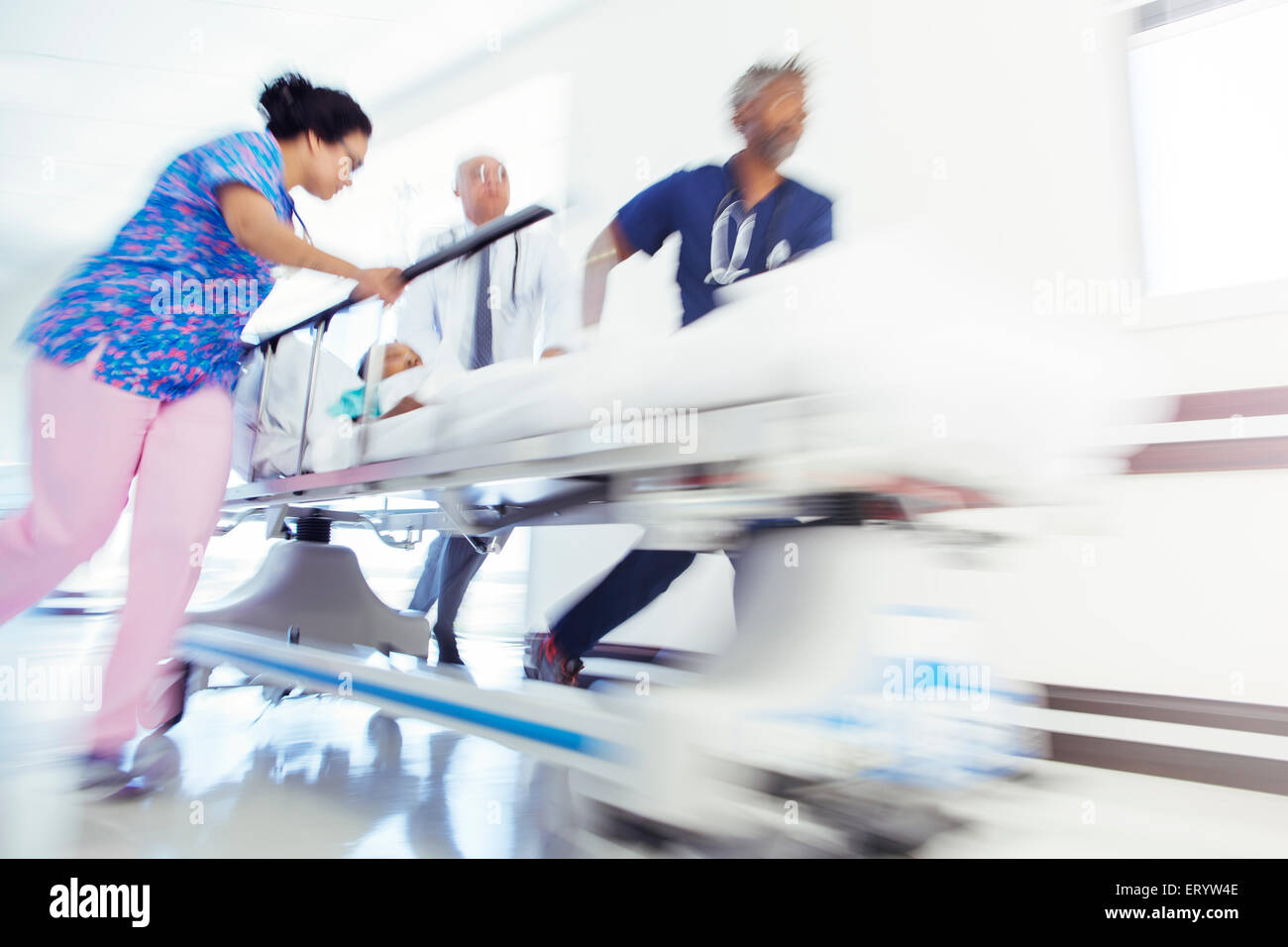 Doctors and nurse rushing patient in stretcher in hospital corridor - Stock Image