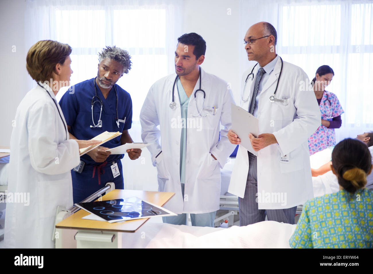 Doctors making rounds and consulting in hospital room - Stock Image