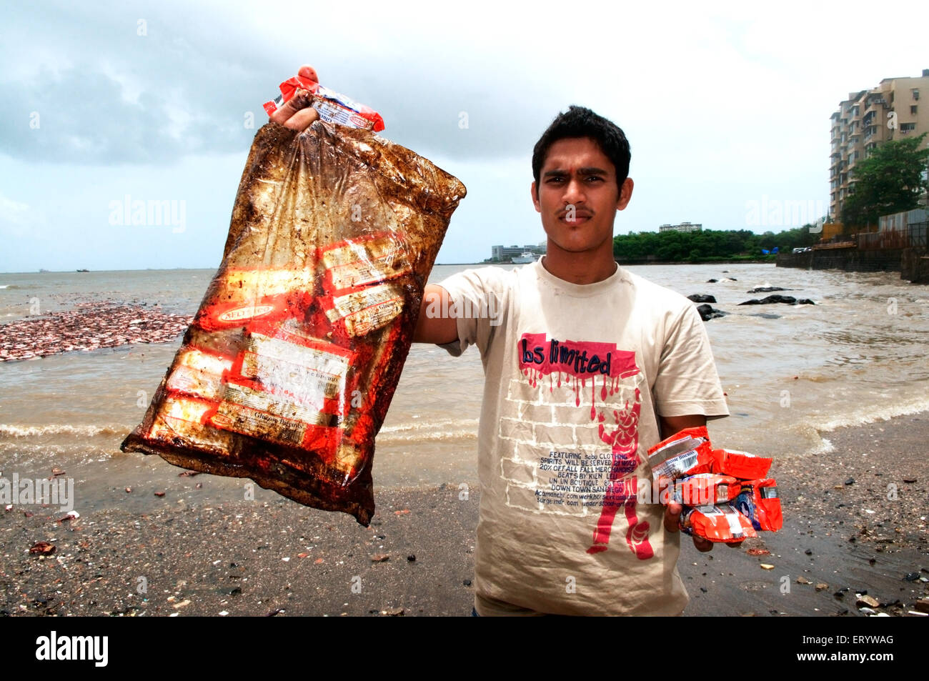 Man showing oil soaked biscuit packets due to oil spill of container ship chitra colliding in sea Bombay Mumbai - Stock Image