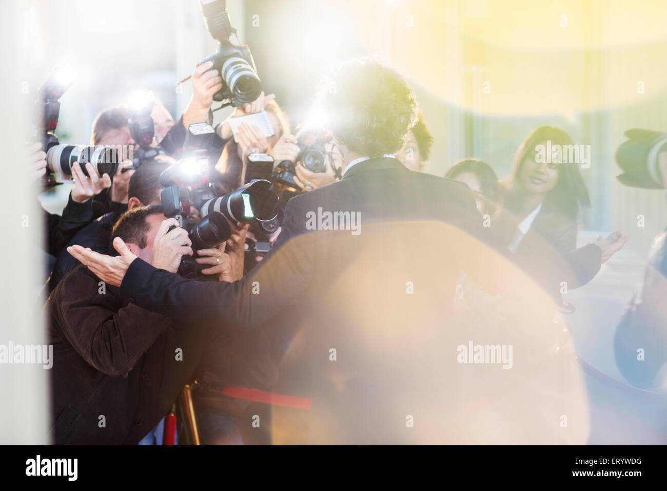 Celebrity being photographed by paparazzi at event - Stock Image