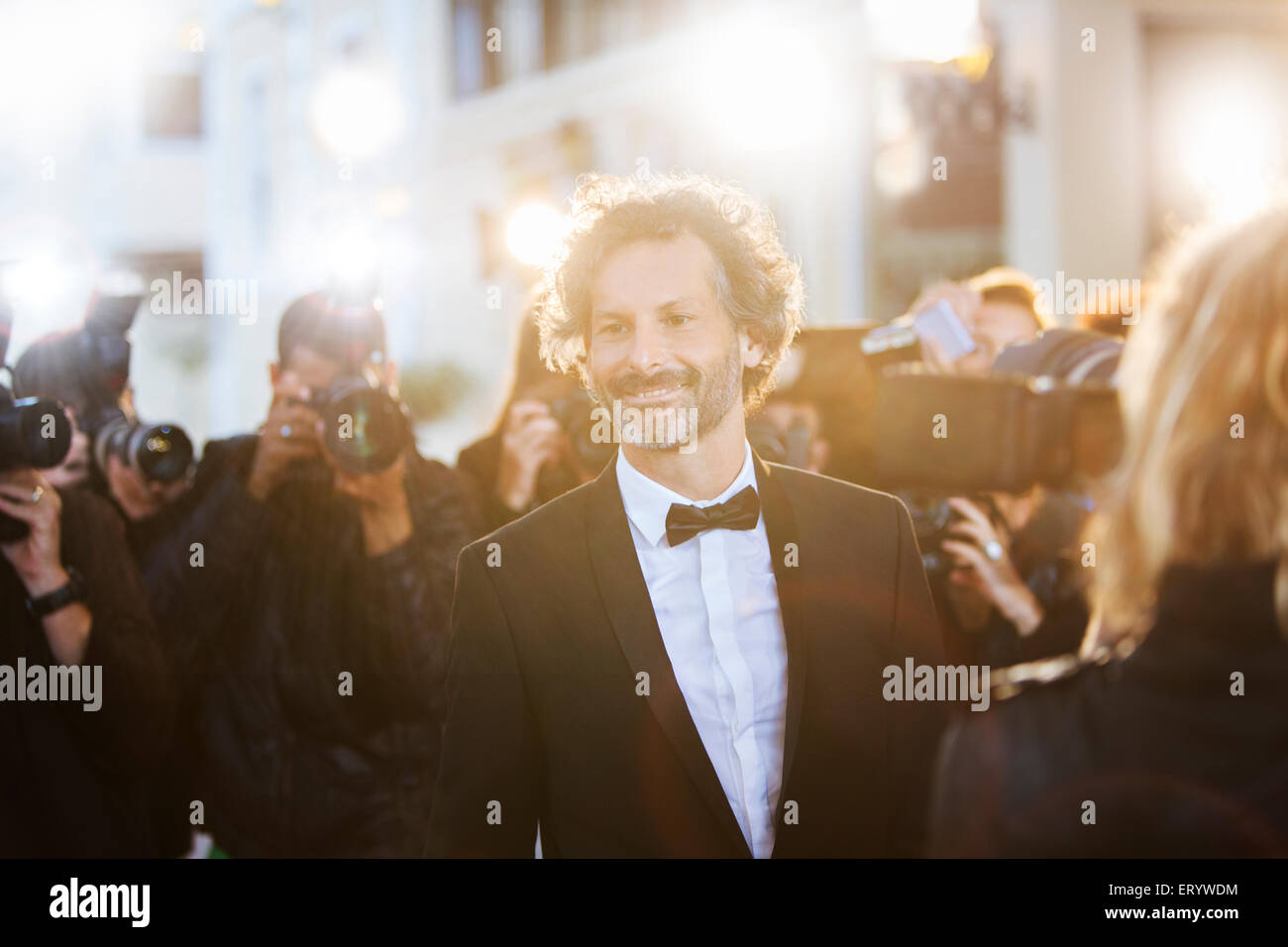 Smiling celebrity being photographed by paparazzi at event - Stock Image