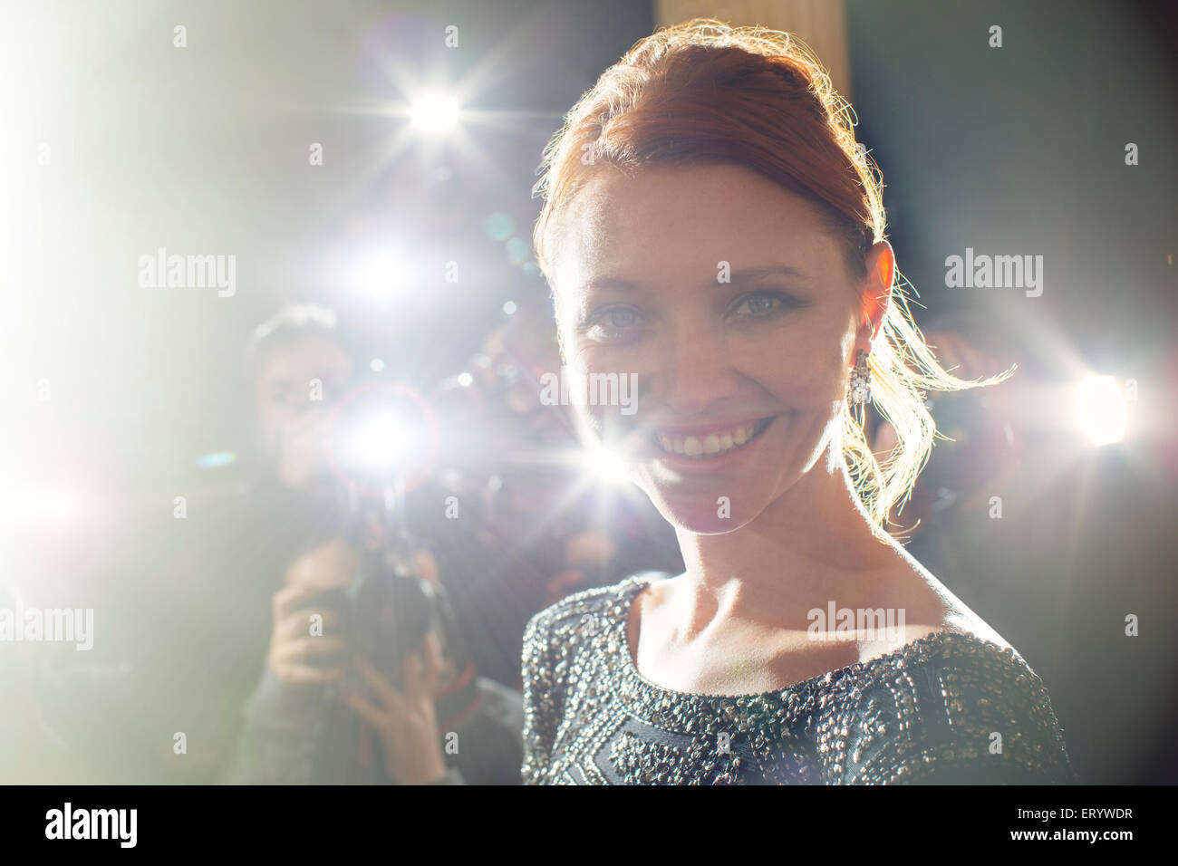 Close up portrait of smiling celebrity being photographed at paparazzi event - Stock Image