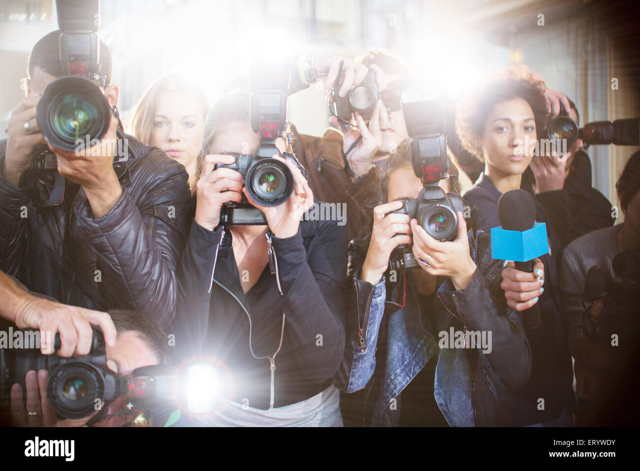 Portrait of serious paparazzi photographers pointing cameras - Stock Image