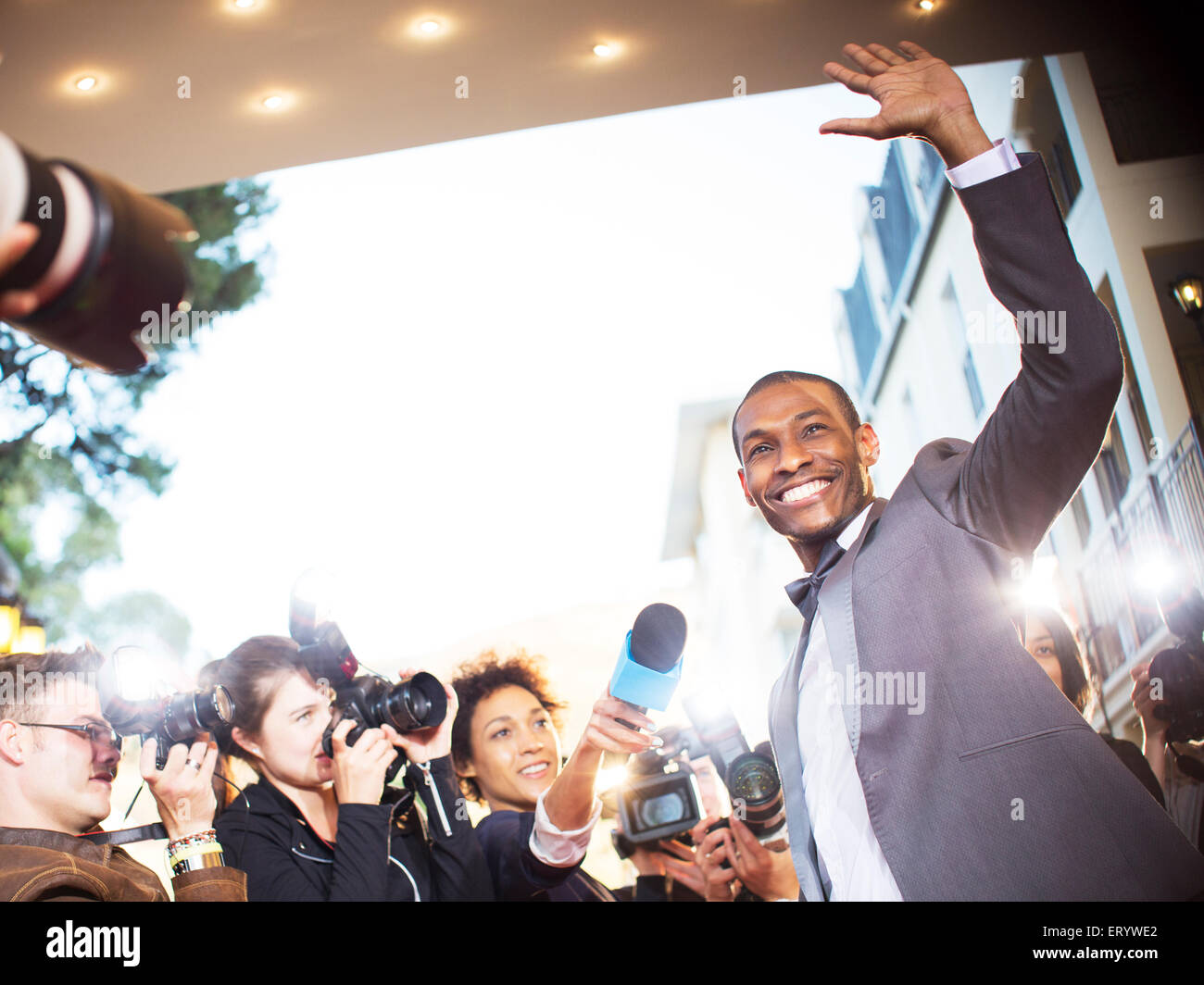 Waving celebrity being interviewed and photographed by paparazzi at event - Stock Image
