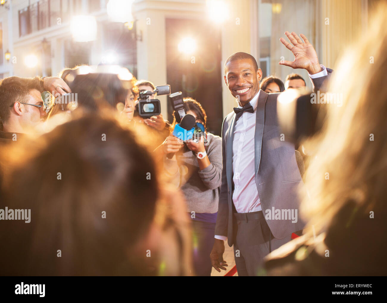 Celebrity waving for paparazzi with cameras at event - Stock Image