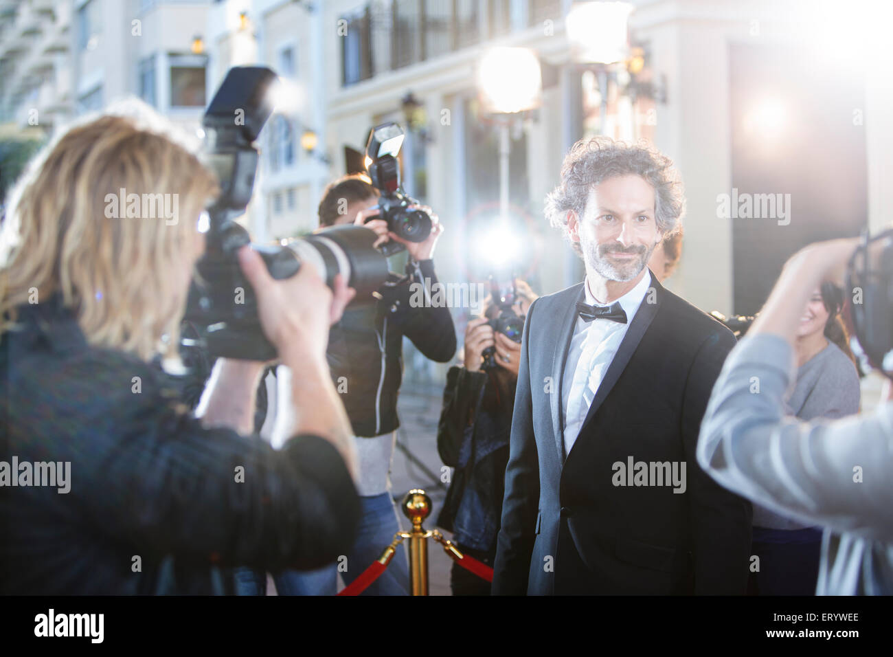 Smiling celebrity in tuxedo being photographed by paparazzi at red carpet event - Stock Image