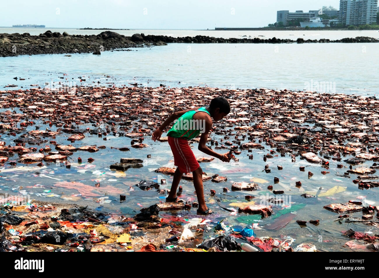 Boy searching biscuit packets from oil soaked  due to container ship chitra colliding in sea Bombay Mumbai - Stock Image