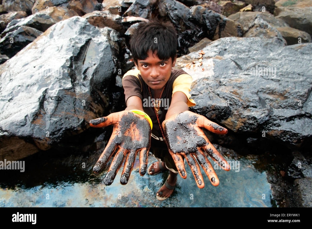 Boy showing oil soaked palm due to container ship chitra colliding in sea Bombay Mumbai ; Maharashtra ; India NOMR - Stock Image