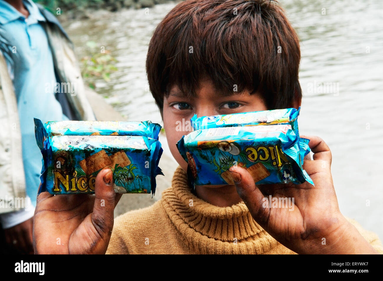 Boy showing oil soaked biscuit packets due to container ship chitra colliding in sea Mumbai ; Maharashtra - Stock Image