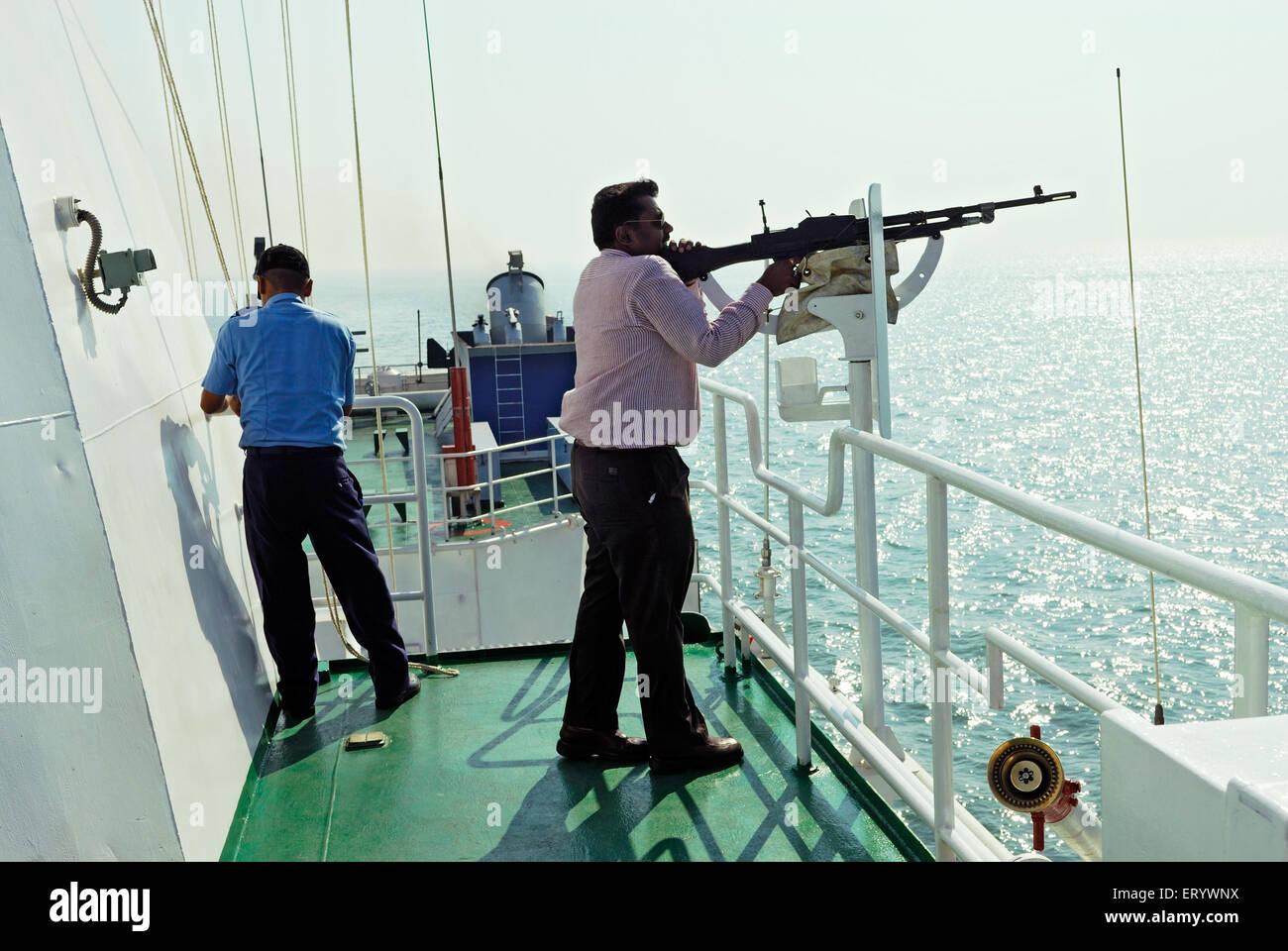 Civilian ; tries his hand on locked machine gun ; Bombay ; Mumbai  ; Maharashtra  ; India - Stock Image