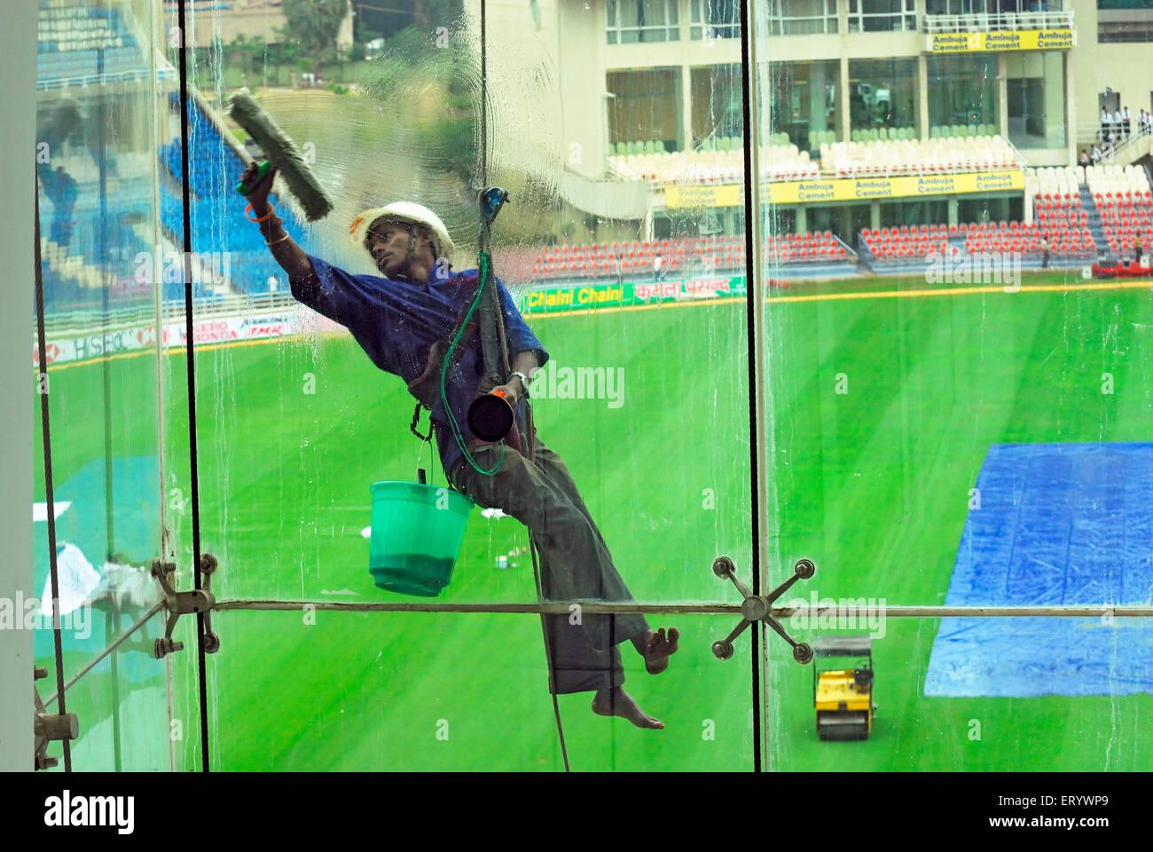 Glass cleaner at D Y Patil cricket stadium  ; Nerul  ; Navi Bombay Mumbai  ; Maharashtra  ; India NOMR - Stock Image