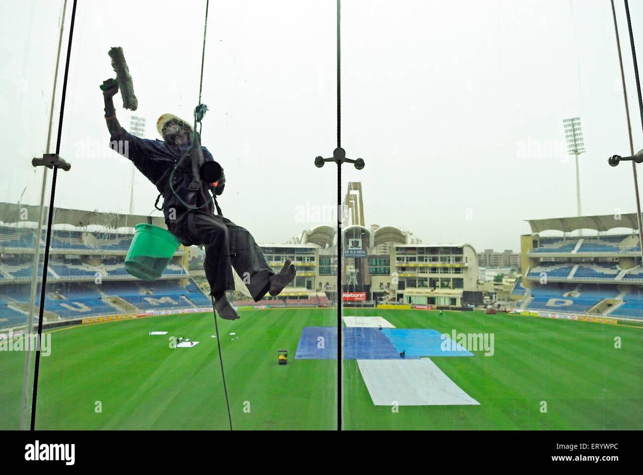 Glass cleaner at D Y Patil cricket stadium  ; Nerul  ; Navi Bombay Mumbai  ; Maharashtra  ; India - Stock Image