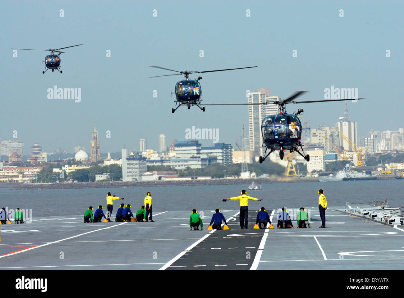 A runway controller indian navy guide chetak helicopter landing deck aircraft carrier INS viraat R22 Mumbai - Stock Image