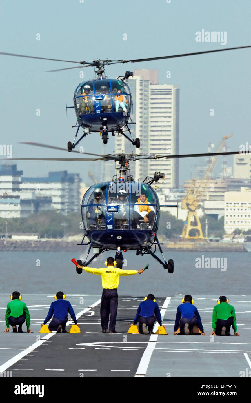 runway controller of indian navy guide chetak helicopter landing deck of aircraft carrier INS viraat R22 Mumbai - Stock Image