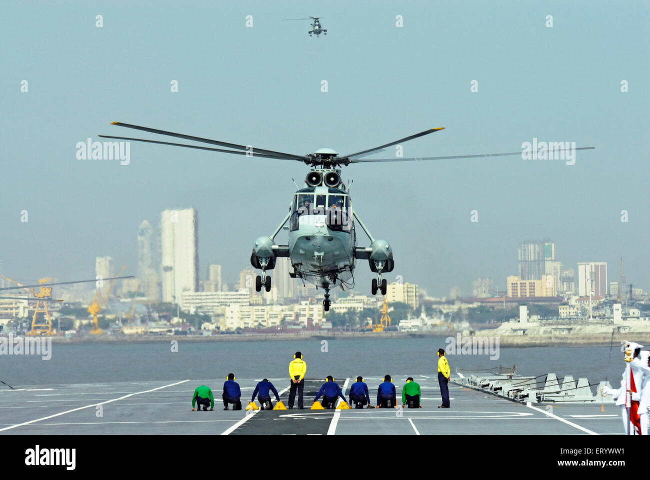 runway controller of indian navy guide MI 18 helicopter landing on the deck of aircraft carrier INS viraat R22 Mumbai - Stock Image