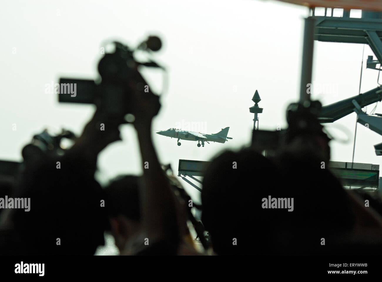 Videographer tries to capture landing of sea harrier ; Bombay ; Mumbai ; Maharashtra ; India - Stock Image