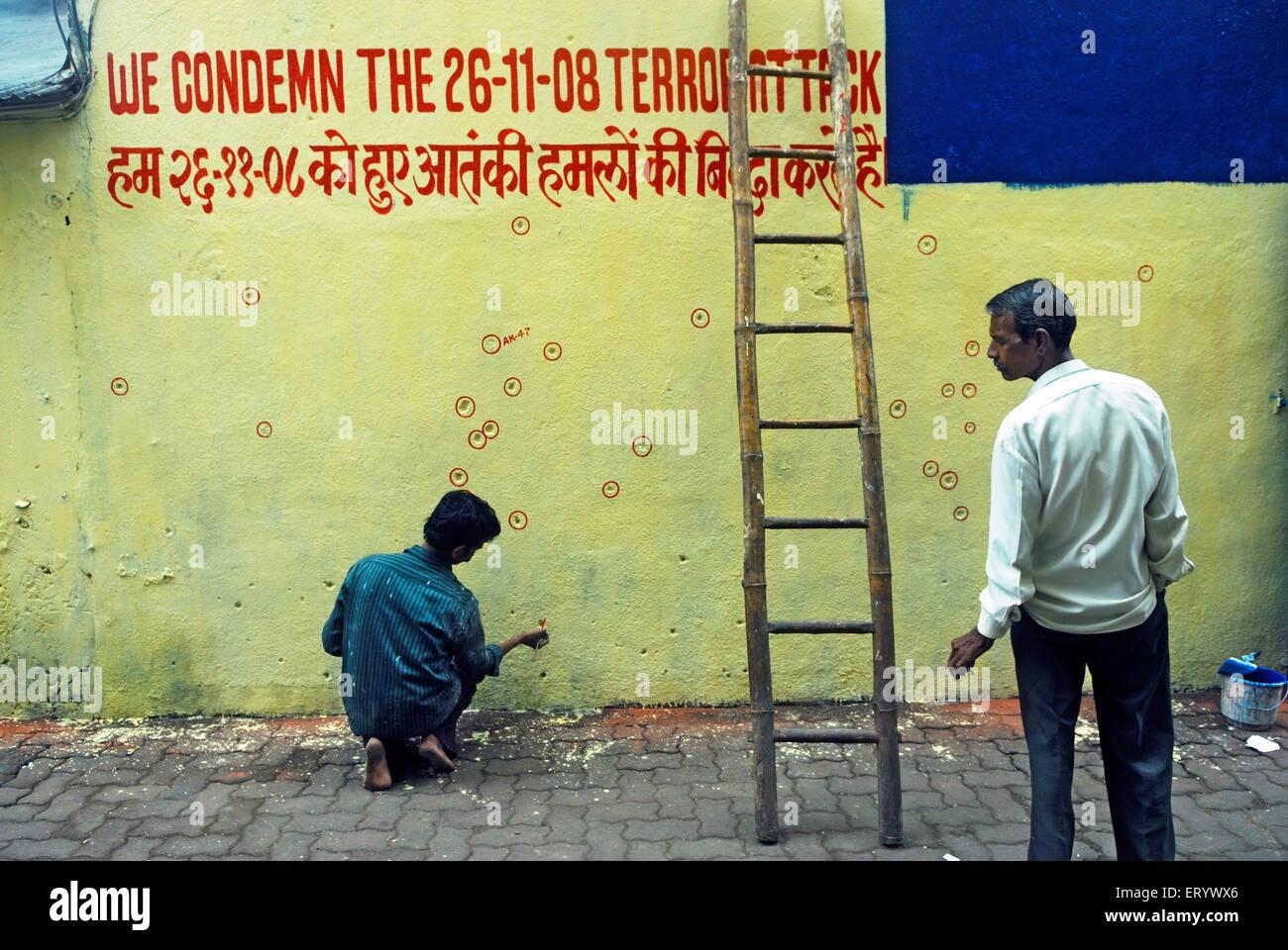 Painter encircle bullet marks on the wall ; Bombay ; Mumbai ; Maharashtra ; India - Stock Image