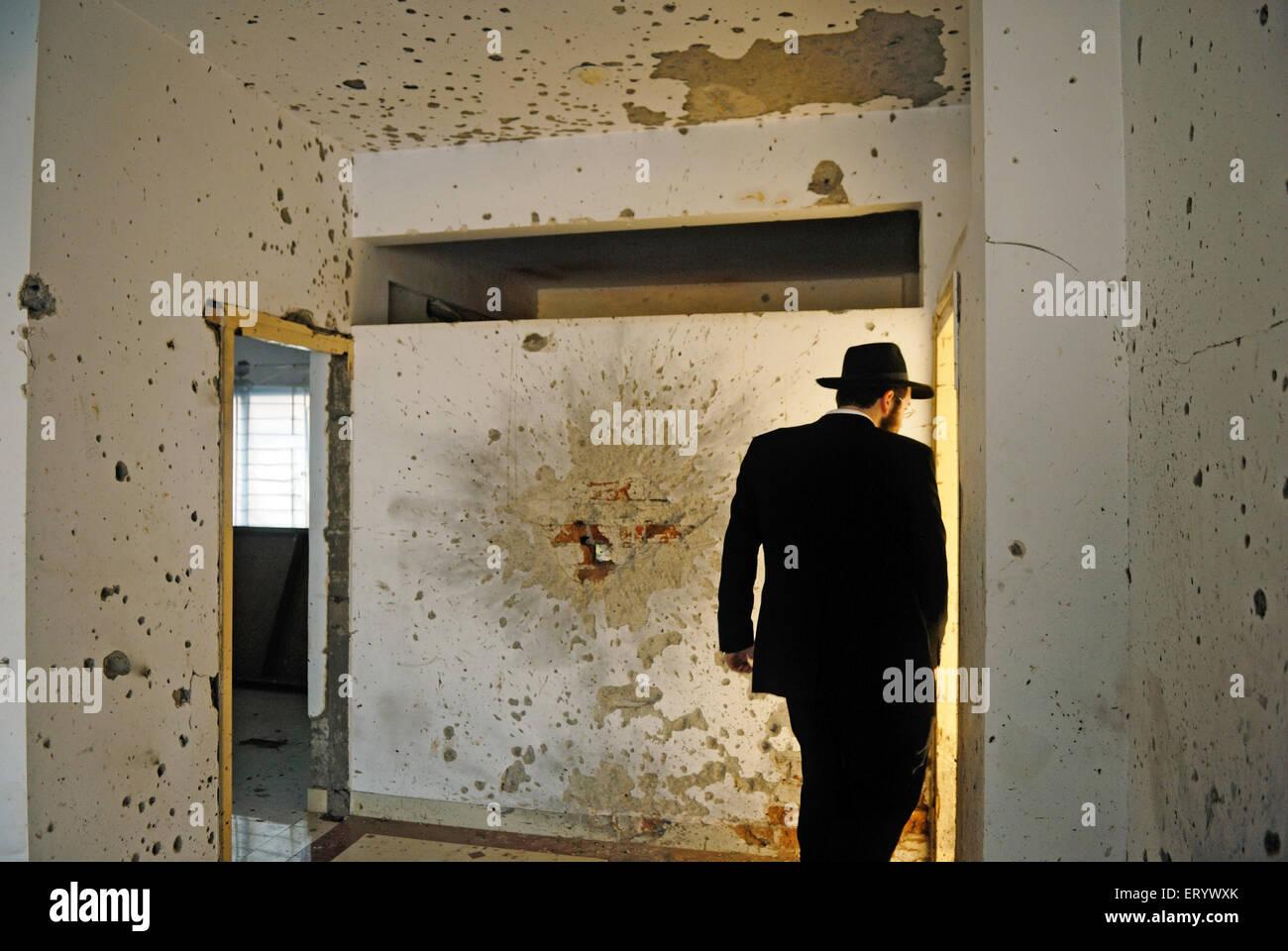 Orthodox jew inspects damaged walls in grenade blast and bullet marks at nariman house ; Bombay Mumbai ; Maharashtra - Stock Image