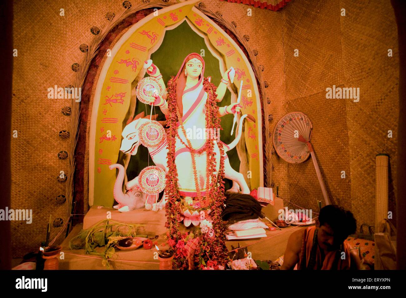 Mother goddess Durga in conventional Bengali sari and in midst of worshipping ; Calcutta ; West Bengal ; India - Stock Image