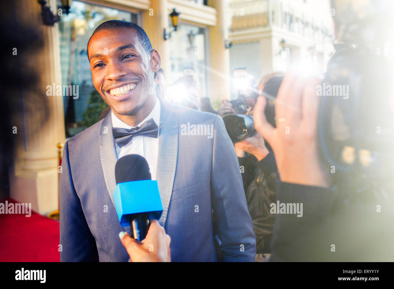 Celebrity being interviewed and photographed by paparazzi photographers - Stock Image
