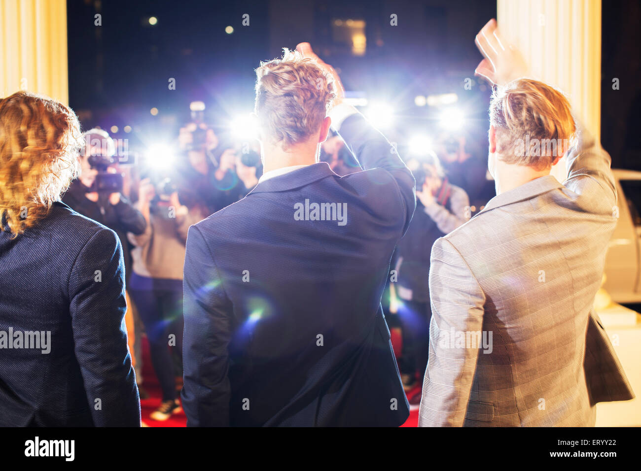 Celebrities waving and being photographed by paparazzi photographers at red carpet event - Stock Image