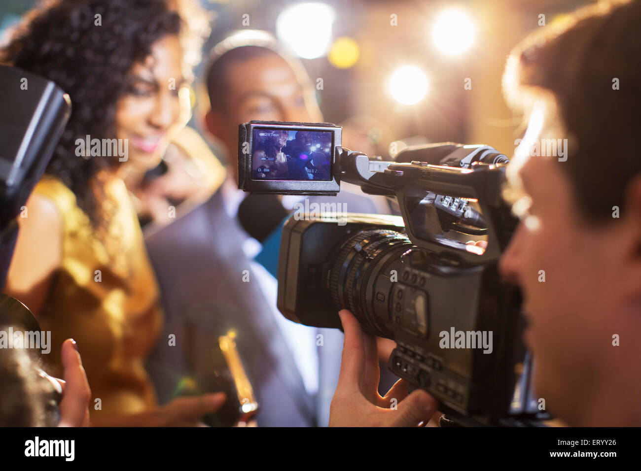 Close up of paparazzi filming celebrity couple at event - Stock Image