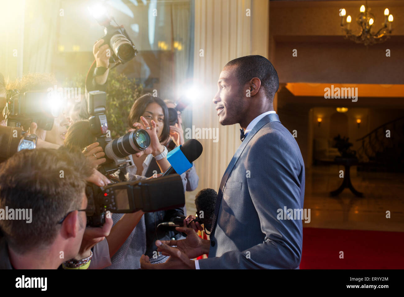 Celebrity being interviewed and photographed by paparazzi at red carpet event Stock Photo