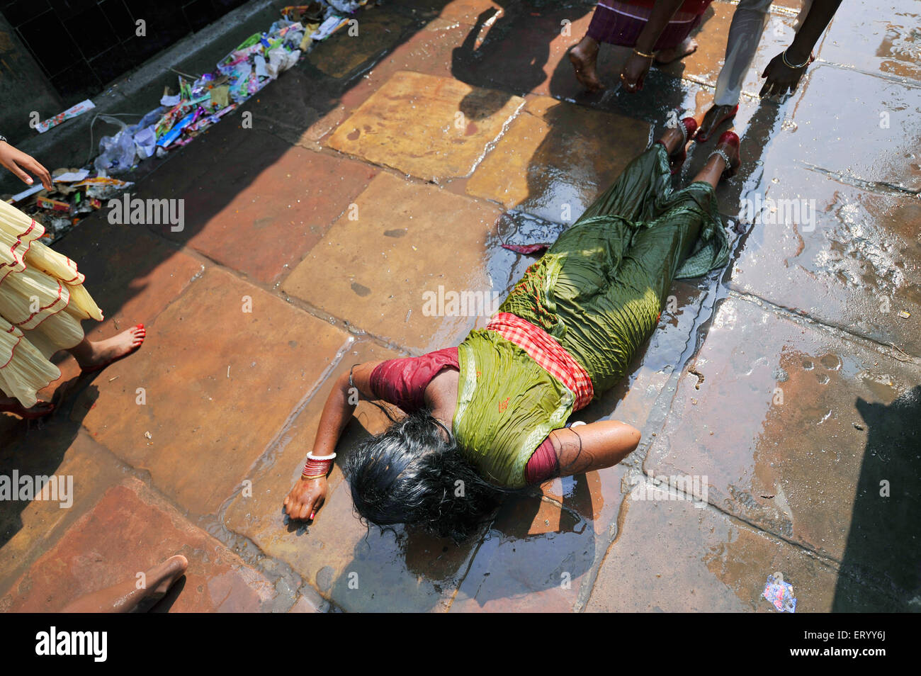 Summer worship by stretching on pavements while water is spread to cool the pilgrims at Kalighat Kolkata India - Stock Image