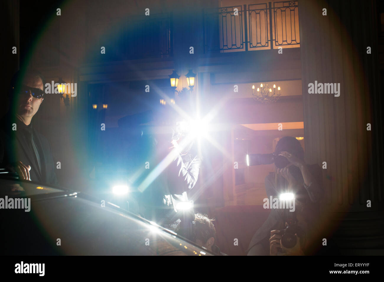 Lens flare from paparazzi photographing at event - Stock Image