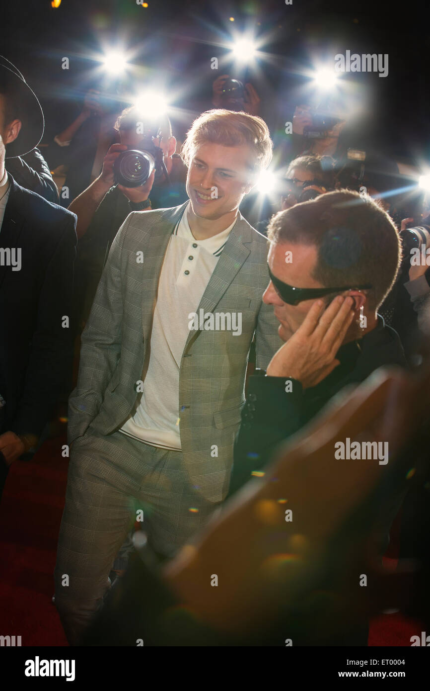 Smiling celebrity arriving at red carpet event and being photographed by paparazzi - Stock Image