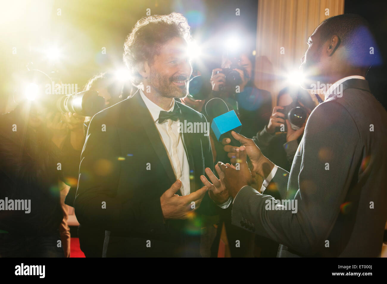 Celebrity being interviewed and photographed by paparazzi at event Stock Photo