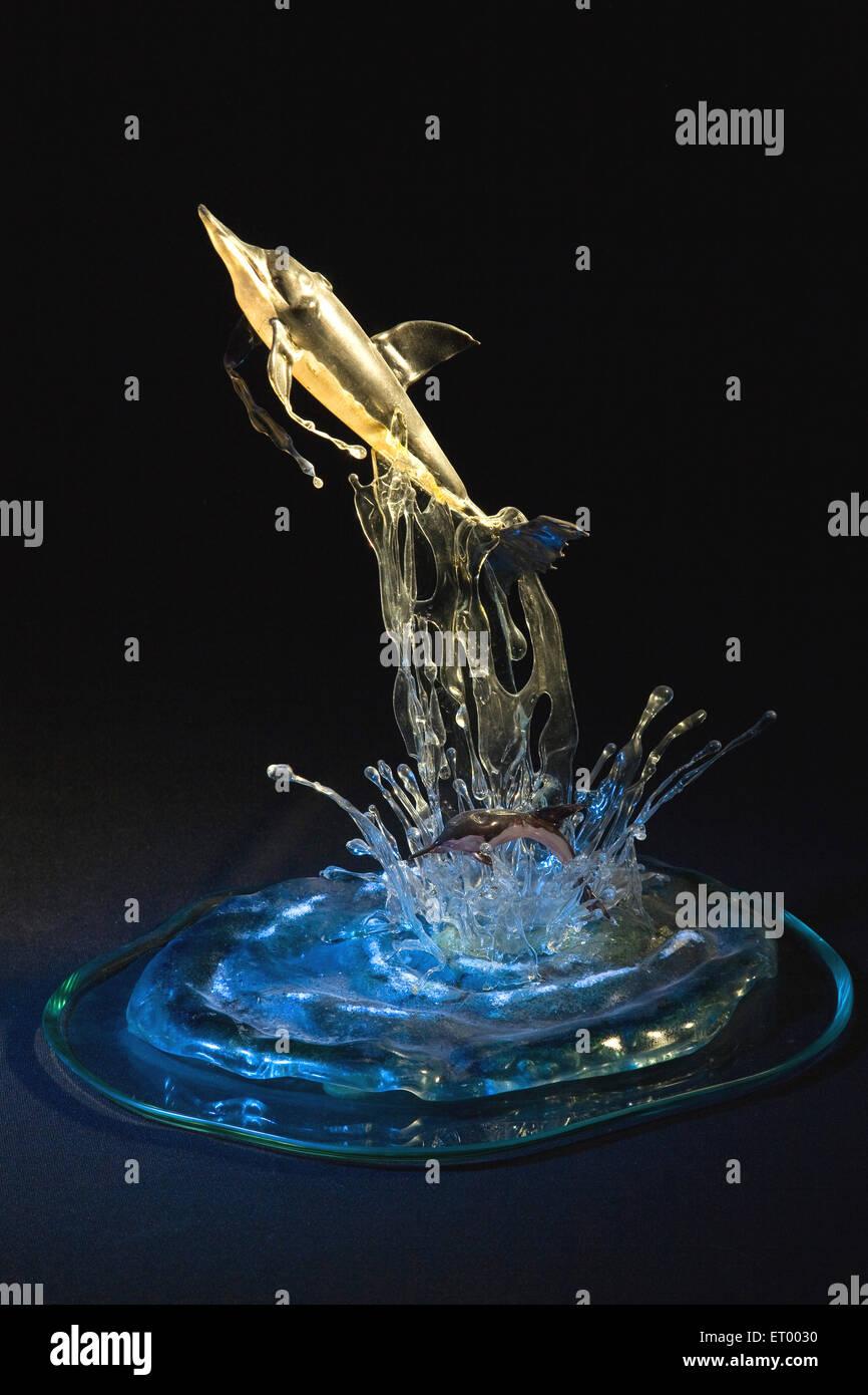 Sculpture of shark glass art on black background - Stock Image