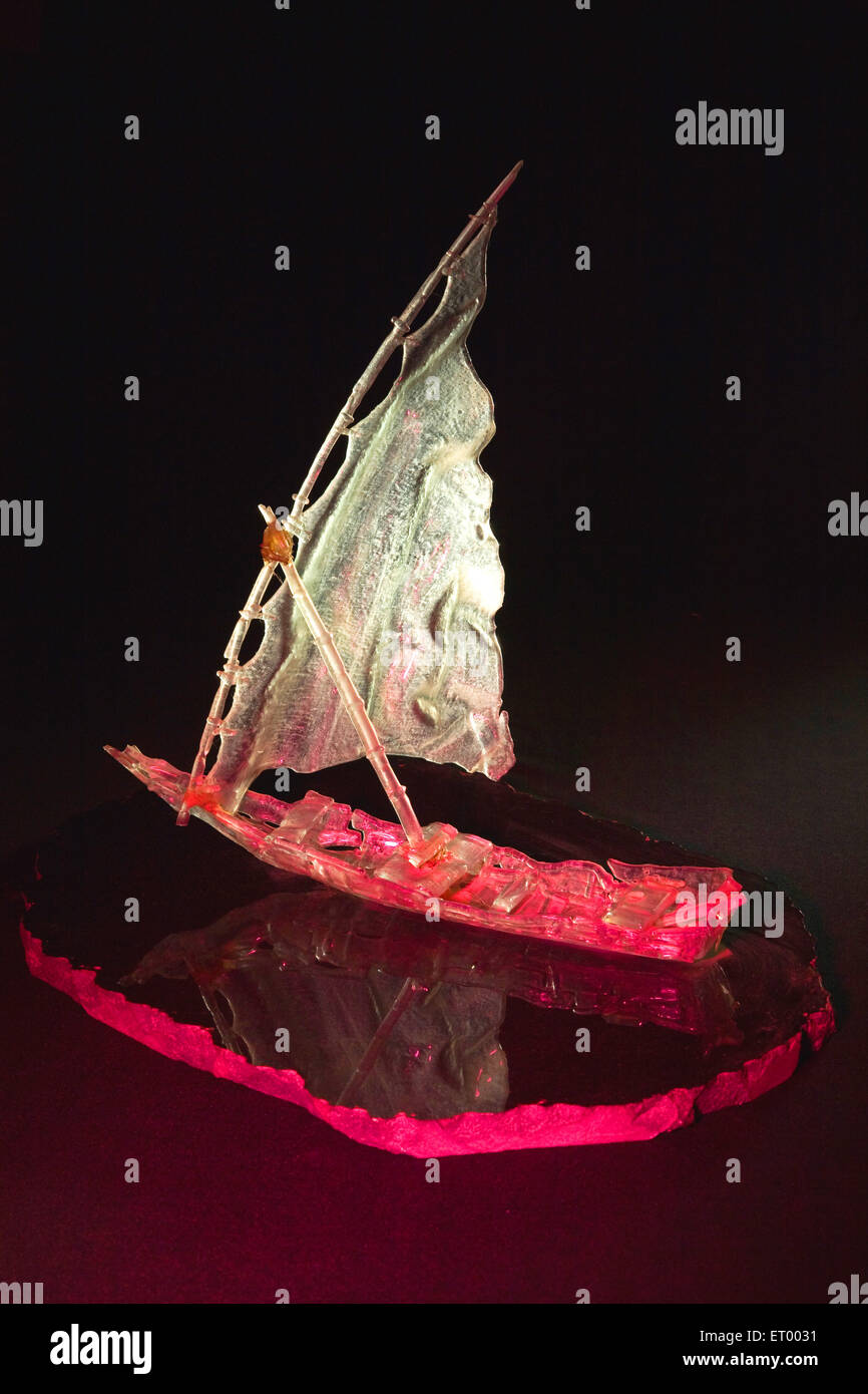 Sculpture of ship glass art on black background ; India - Stock Image